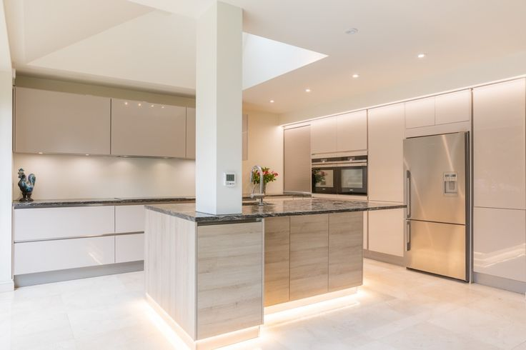 Kitchen island design incorporating a large central pillar through the island, saving on floor space elsewhere.