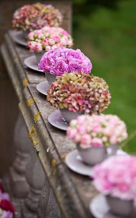 Flowers in Tea Cups - Great Centrepieces. Simple to do, less expensive than big bunches of flowers and you can make then into favors for guests to take home. Place a small tag on the handle with the female guests names on.