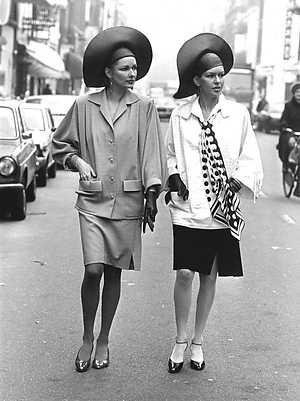 Presentatie voorjaars/zomermode 1982 Edgar Vos. Tanja (r) draagt een wit/zwart linnen tailleur met verbrede schouders een…