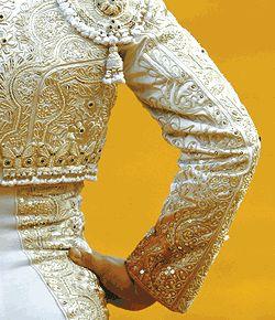El la corrida de toros, todos los matadores llevaban trajes de luces. Cuando Juan Cortez entró, Carmen le dijo a Ana que Juan Cortez es mucho atractiva porque el llevaba un traje de luces.