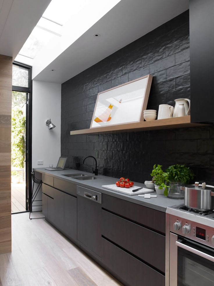 Moderne zwarte keuken met glanzende tegels op de achterwand.