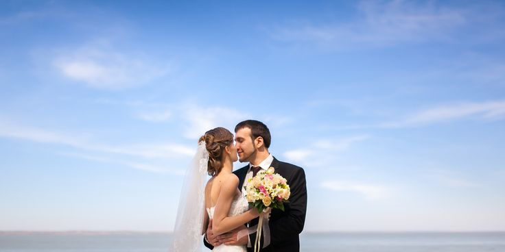 Жених и невеста лицом друг к другу. Жених обнимает невесту за талию.