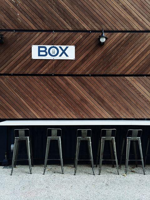 Wall / ilili Box, NYC. Diagonal wood wall, metal stools.