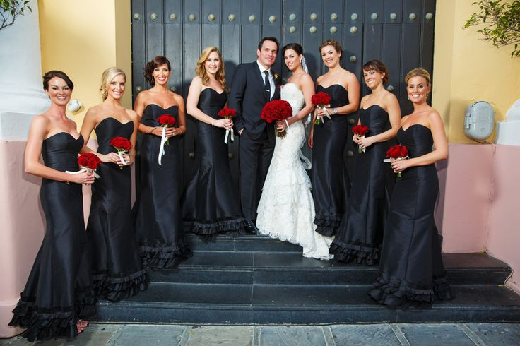 Wearing Alvina Valenta style 9161, real bride Carissa poses with husband Greg and her bridesmaids in black Alvina Valenta dresses style 9128