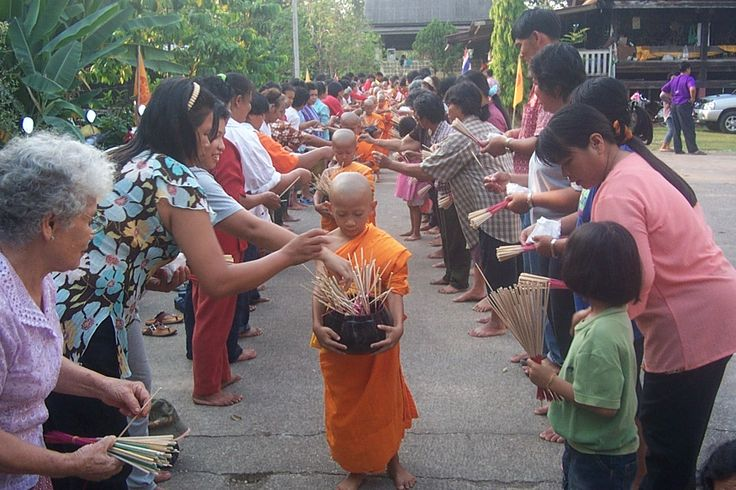 Thai People Worshipping | Buddhist novices receiving joss sticks .