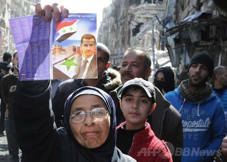 シリア国営シリア・アラブ通信(Syrian Arab News Agency、SANA)が公開した、首都ダマスカス(Damascus)南部にあるヤルムーク(Yarmuk)パレスチナ人難民キャンプでバッシャール・アサド(Bashar al-Assad)大統領の写真を掲げる女性の写真(2014年2月24日撮影)。(c)AFP/SANA ▼28Feb2014 AFP 4万人餓死の危機、シリア・ヤルムーク難民キャンプ http://www.afpbb.com/articles/-/3009500 #Syria #Siria #Syrie #Syrien #Yarmuk