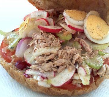 """Le pan bagnat, dont le nom signifie """"pain mouillé"""" en niçois, est un sandwich à base de crudités et d'huile d'olive. Nous vous proposons de découvrir la véritable recette de ce casse-croûte complet et facile à emporter."""