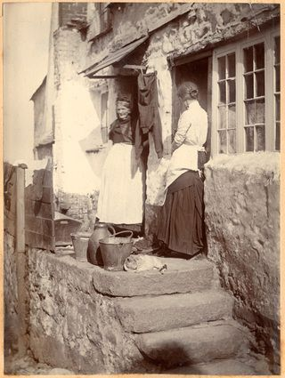 A photograph of an older and a younger woman talking on the steps of the entrance of two terraced cottages in Newlyn. In front of them are two pails, a bussa and a sleeping cat. Clothes hang out to dry between the two doors and on the wooden fence to the left. Both wear aprons tied in two places at the back. - Collections - Penlee House Gallery and Museum Penzance Cornwall UK