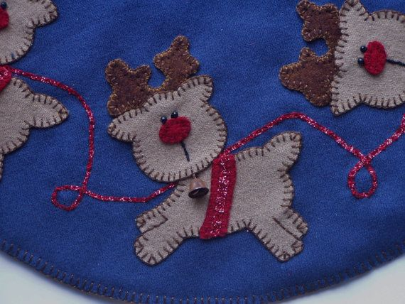 This beautifully hand stitched Christmas table mat/penny rug is full of festive reindeer just in time for the holiday season. Made from felted wool, every reindeer has been blanket stitched to a slate blue wool base. Each has reins and a harness made with delicate glitter ribbon whip stitched in place. They have little black beads for eyes and a bright red wool nose. Around the neck of all the little reindeer is a rusty liberty bell. The top was then sandwiched with dark cotton batting a...