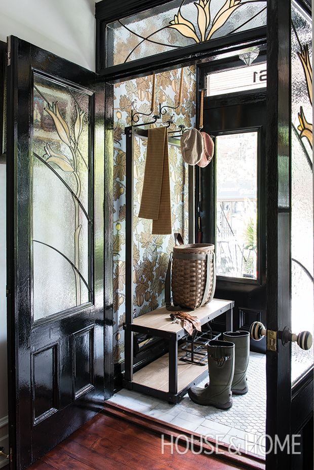 This welcoming space by Les Ensembliers makes a great first impression with bold black-painted doors and a whimsical nature-inspired wallpaper.   Photographer: Andre Rider