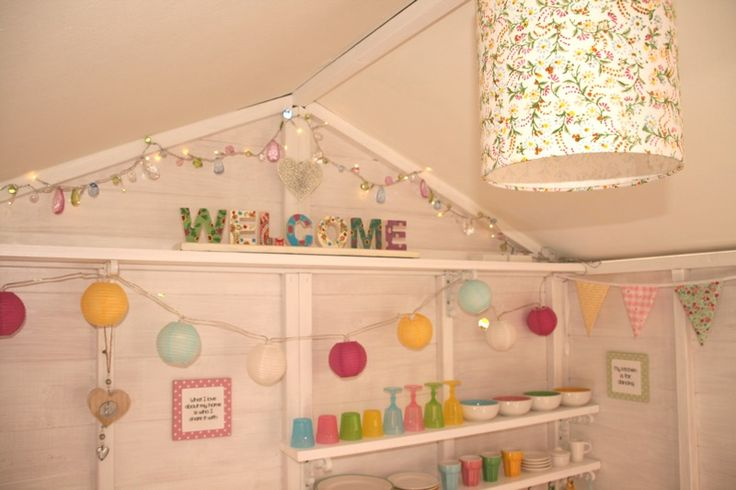 Decorated playhouse interior with lights & shelves.