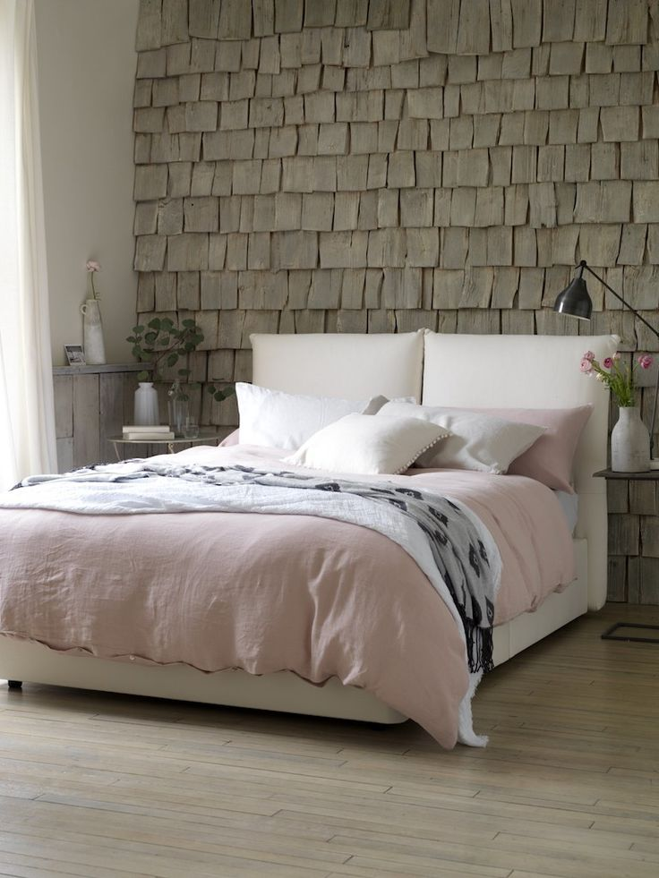 A hygge style bedroom with light pink blanket, modern bedside tables and extraordinary textured wall
