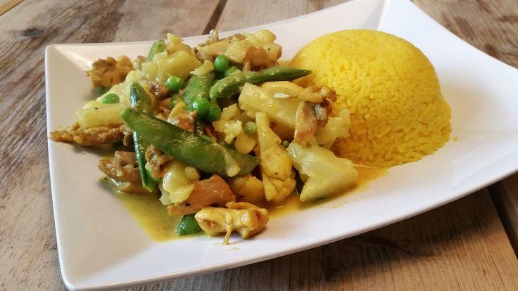 Recept voor gele rijst in een kerrie-kokossaus met gemarineerde kippendijen, bloemkoolroosjes, sugarsnaps, doperwtjes en ananas