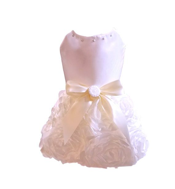 Handmade dog dress constructed from ivory satin fabric with Ivory rosette skirt.. Accented ivory satin bow and pearl button at waist. Further embellished with small pearls at neckline. This dress is perfect for any formal occasion or for the brides who want to include their furbaby