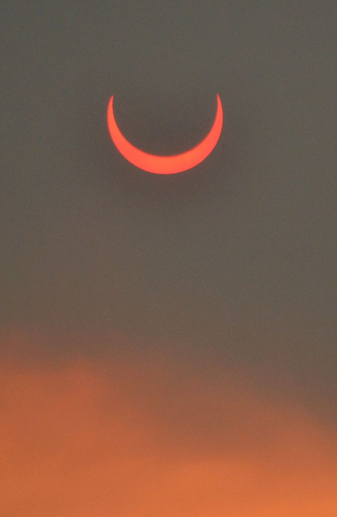 Annular eclipse seen through smoke from the Arizona wild fires, by Melissa McCollum, on flickr.