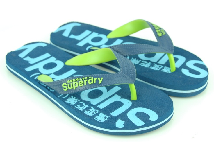 SUPERDRY! Coole teenslipper van Superdry in jeansblauw met licht blauwe letters. In de zool zit nog een licht blauw randje. De teenslipper heeft fel groene highlights en het geheel is van rubber.  maatindeling= 41  = 41 + 42 = S 43 = 43 + 44 = M 45 = 45 + 46 = L