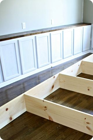 Wall of bookshelves and cabinets from Thrifty Decor Chick: step 3- adding butcher block countertop