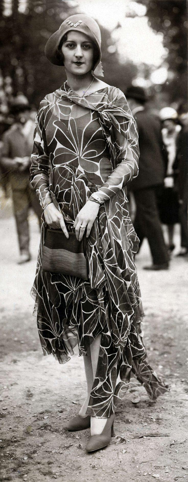 14-11-11  Damesmode. Modeshows van de grote couturiers tijdens de paardenrennen zijn populair. Dit model toont een creatie uit de zomermode collectie van 1929. Een japon van dunne stof en met een ongelijkvallende rok.Ze draagt daarbij een tas en een hoedje. Compiègne, Frankrijk, 1929.