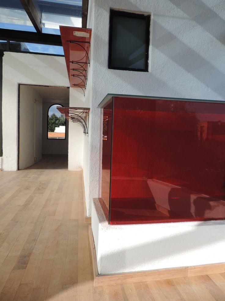 Se fabrico una mesa de vidrio serigrafiado color rojo sobre un tragaluz existente, con el fin de mantener la funcionalidad del tragaluz y tener una mesa para la terraza, las repisas son vidrio craquelado color rojo y en el piso se coloco duela de madera natural.