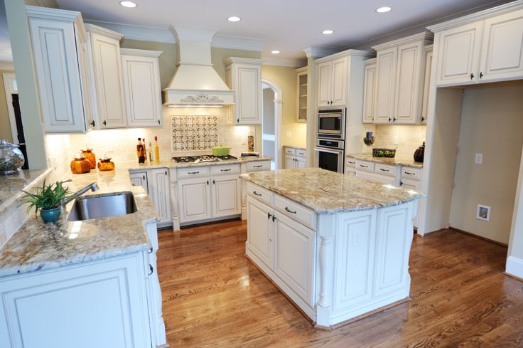 Another white kitchen, this space centers around large marble topped island over natural hardwood floor.