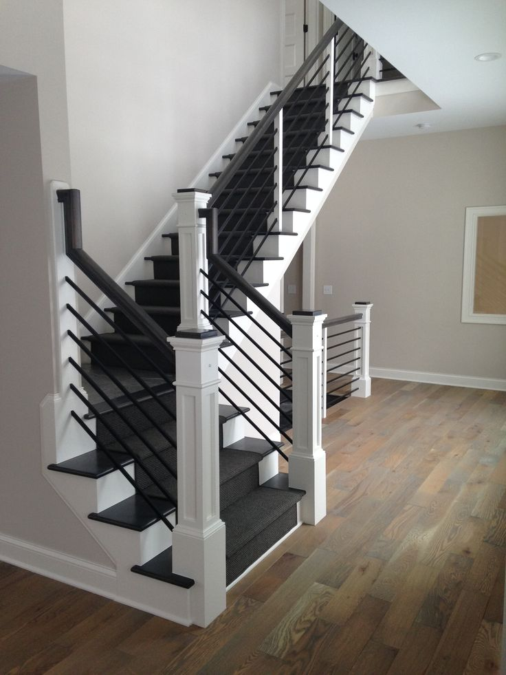 These black stairs covered with a charcoal grey runner really make the lighter hardwood floors POP!