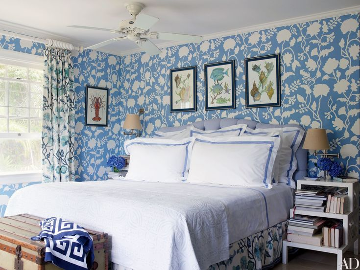 The blue master bedroom of a cottage in the Bahamas by Andrew Raquet Interior Design  took shape around an Alan Campbell wallpaper; the fan is by Hunter, the headboard is by Avery Boardman, and the bed linens are by Matouk and D. Porthault.