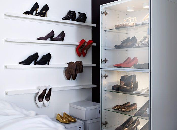 BESTÅ Regal mit Glastüren in Weiß und seitlich davon RIBBA Bilderleisten in Weiß an der Wand; alles als Aufbewahrung für Schuhe genutzt