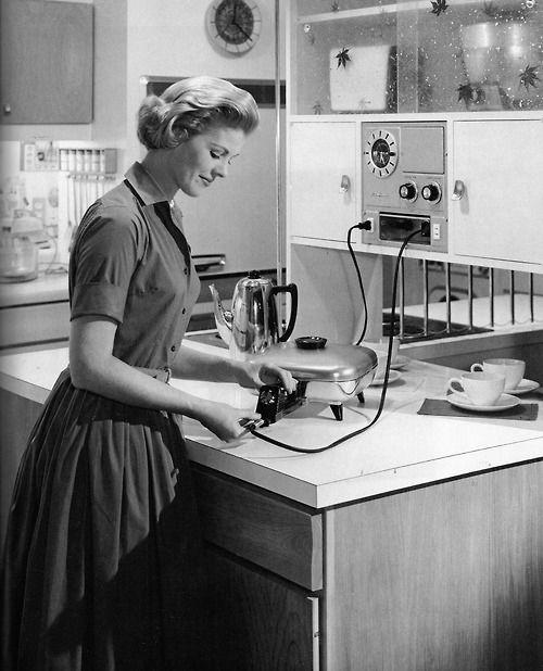 A dona de casa dos anos 1950, preparando-se para preparar uma refeição com os modernos aparelhos elétricos.