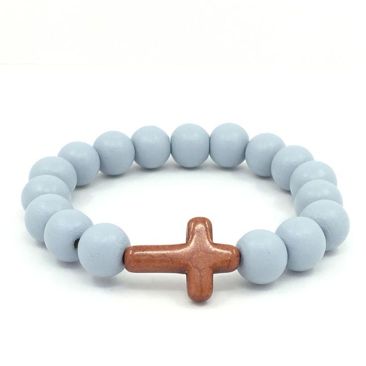 Cross your arm - Lichtblauw & bruin  Houten kralenarmband in de kleur lichtblauw met grote kralen (12 mm), gecombineerd met een keramiek kruis kraal in de kleur bruin (afmeting ca. 24 x 18 mm).