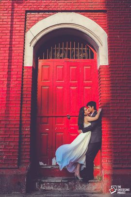 Indian Wedding Photography - Red Themed Couple Pre-Wedding Photography | WedMeGood Beautiful pre-wedding shot of couple hugging in front of a red door. #wedmegood #indian #wedding #photography