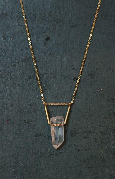 Collier sur chaîne fine dorée avec un cristal de roche traversé par une chaîne et surmonté de deux perles en tube.    Chaque cristal de roche est u...