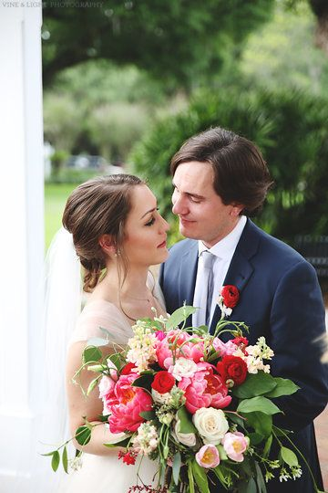 the groom wears a red ranunculus boutonnière to compliment his brides' bouquet of coral charm peonies, red ranunculus, Vendala roses, hot pink ranunculus, light pink lisianthus, jasmine vine, lemon leaf, peach stock & seeded eucalyptus wrapped in cream muslin ribbon