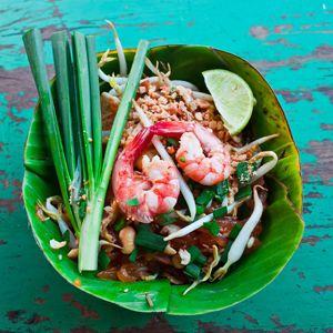 """Iedereen die in Thailand is geweest, kent de eetkraampjes op iedere hoek van de straat waar de meest heerlijke geuren vandaan komen. Pad Thai is typisch """"streetfood"""", recht voor je neus wordt in enkele minuten Thailand's nationale gerecht voor je klaargemaakt en geserveerd in een bananenblad of krant. Essentieel voor de Thaise keuken en dus ook voor Pad Thai is de balans tussen zoet, zout en zuur dus lekker veel proeven tijdens het koken!"""
