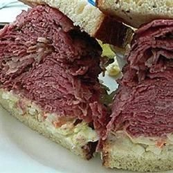 Slow Cooked Corned Beef for Sandwiches  2 (3 pound) corned beef briskets with spice packets  2 (12 fluid ounce) bottles beer  2 bay leaves   1/4 cup peppercorns  1 bulb garlic cloves, separated and peeled   4 hours minimum