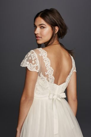 Give a strapless gown a cap sleeve option with a beautiful lace overlay topper.  Cap sleeve topper with sheer illusion lace applique and ribbon trim at waist.  Sizing: 0-26.  Dry clean only.  Available in Soft White.  Imported.