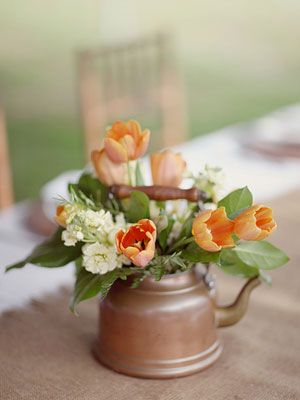 Though we love glass vases and Mason jars, creative containers like watering cans, copper teakettles and tin cups can add a perfect vintage touch to your reception decor.