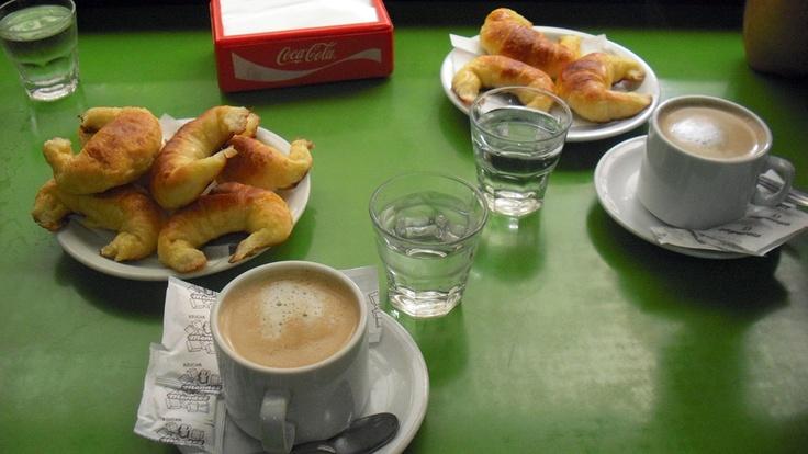 desayuno argentino. café con leche, agua y tres medialunas   tipica colazione argentina.