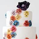Multicolored pansies and a chocolate bottom layer add  visual interest to this three-tiered wedding cake