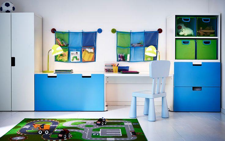 Ein Kinderzimmer mit STUVA Aufbewahrung mit Bank in Weiß/Blau, MAMMUT Kinderstuhl in Hellblau, KUSINER Fächern in Grün/Türkis, KUSINER Wandaufbewahrung in Blau und LILLABO Spielteppich in Grün