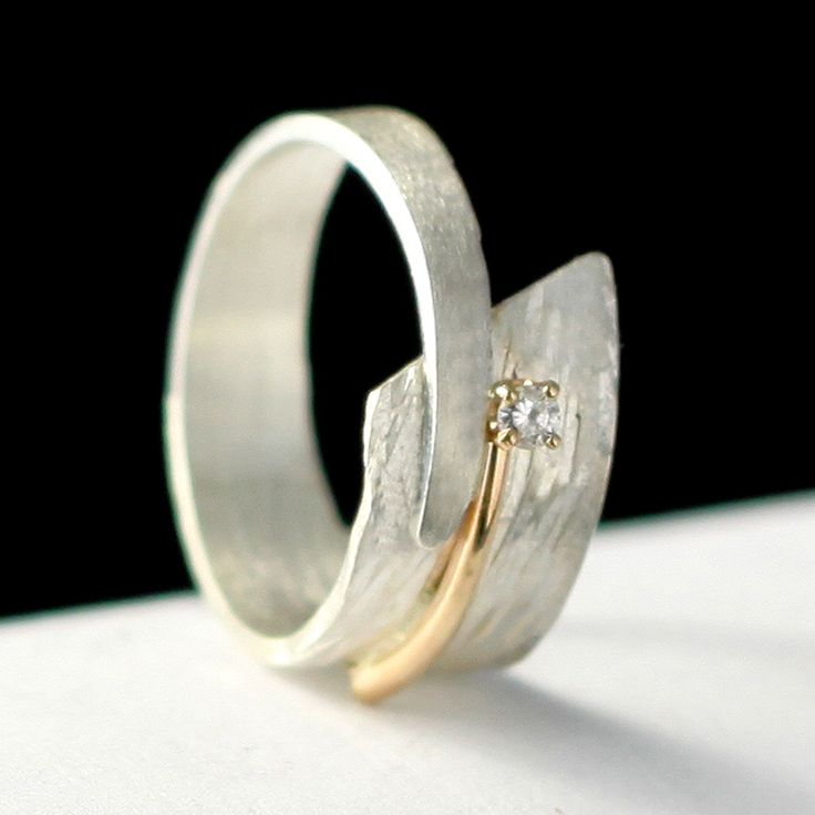 Circle of Love by Dagmara Costello. Sterling silver and 14kt yellow gold hand created ring adorn with .10ct brilliant cut diamond set in four prong head. Available in sizes from 4-11.