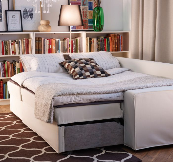 ikea sofabed made up as a double bed at night floor lamp behind