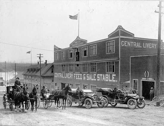 Photograph shows various vehicles near the corner of Eighth Street and Columbia Street circa 1910. In the backgound is the Central Livery Feed and Sale Stable [Thompson's Livery]. [ca. 1910] IHP0090