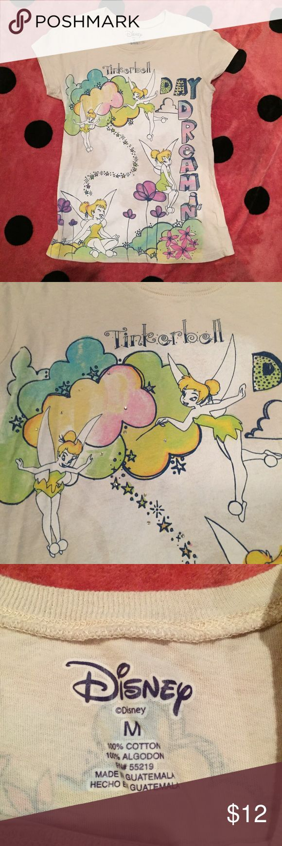 """Disney Tinkerbell Day Dreamin Graphic T-shirt In excellent used condition from Disney. It is a cream colored t-shirt with a printed Tinkerbell """"Day Dreamin"""" graphic on the front and small graphic on the back. Light fabric wear and no holes or stains.   Reasonable offers welcome and I do not trade. 15% discount on bundles of 2 items Disney Tops Tees - Short Sleeve"""