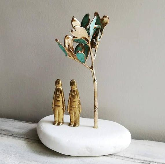 Two men sculpture. brass men figurines under tree mastic tree