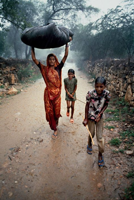 Steve McCurry, INDIA. Monsoon, 1983. A family walks down a road in the rain. More