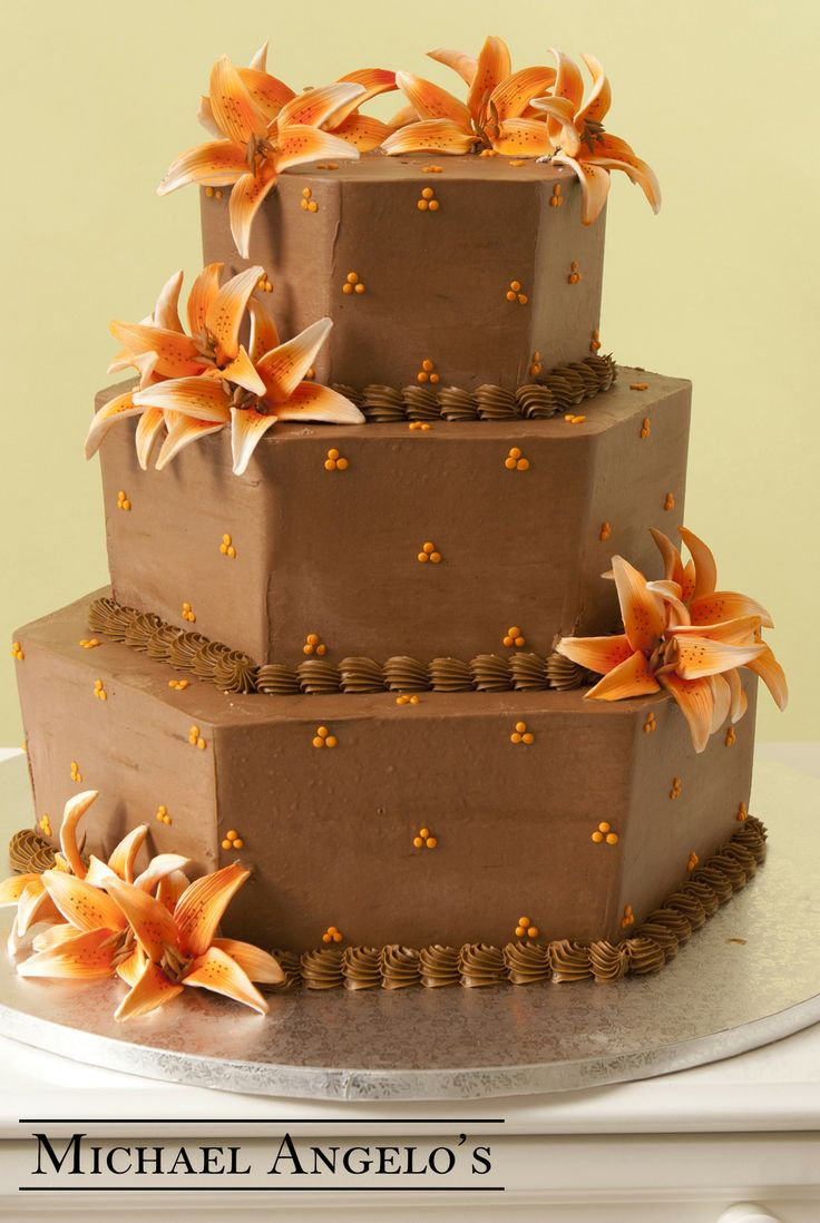 Chocolate Tiger Lillies #29Specialty  This cake is iced in chocolate buttercream for all those chocolate lovers! The orange lillies and petite polka dots make great accents to this hexagon shaped design. The colors can be changed to match your wedding.