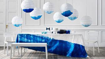 Dinnerparty mit weißen REGOLIT Hängeleuchtenschirmen über dem Tisch, die teilweise blau eingefärbt wurden, und blauem TRIVSAM Geschirr und b...