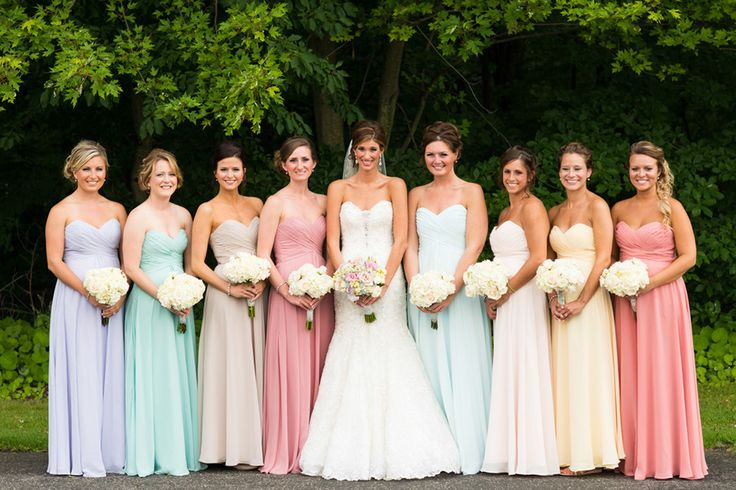 """To tie into the wedding's """"earthy rainbow"""" theme, Brooke's bridesmaids donned long, strapless, chiffon dresses in a spectrum of pastel hues that created a rainbow effect when they stood side by side."""