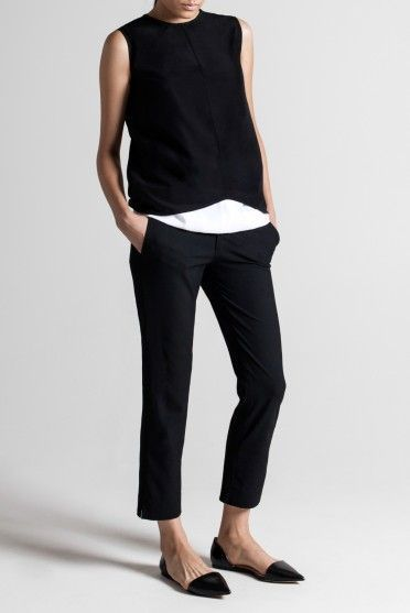 Minimalist chic: Black sleeveless top over simple white shirt, black ankle pants…