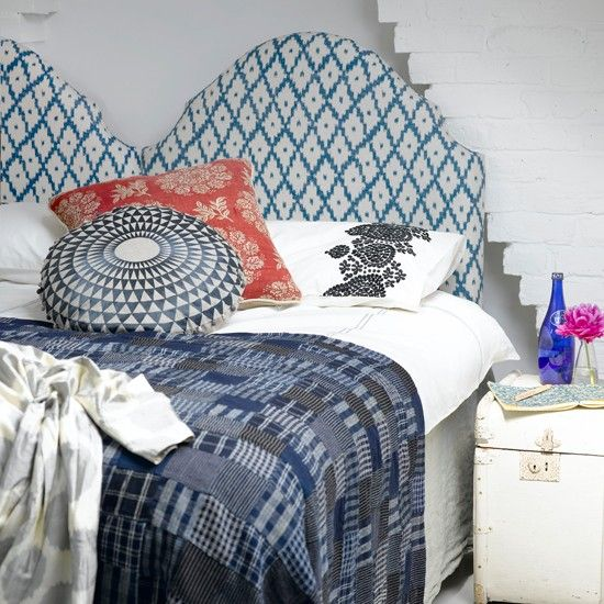 Double bed with padded and patterned headboard, bedside table and cushions